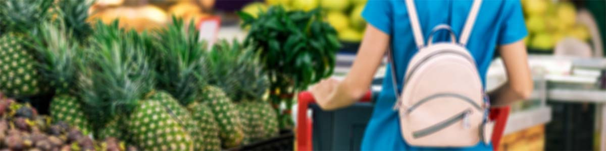 Woman with shopping cart looking at pineapples in a grocery store