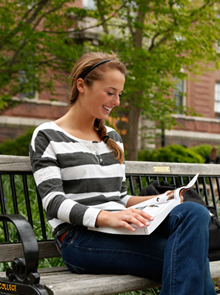 Smiling student reading book on bench